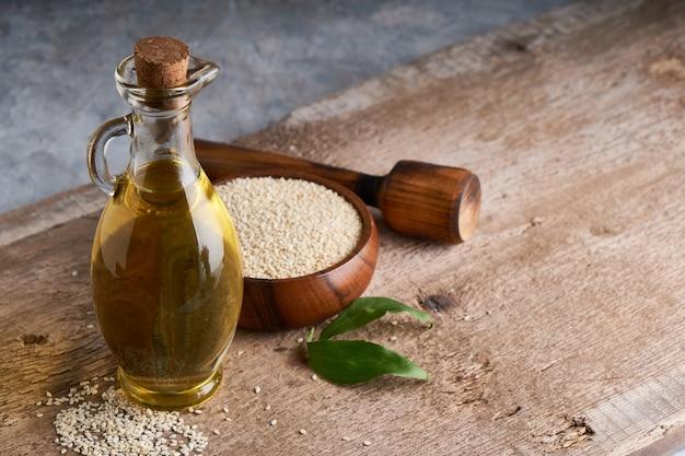 Óleo de gergelim em frasco de vidro e sementes de gergelim na mesa de madeira