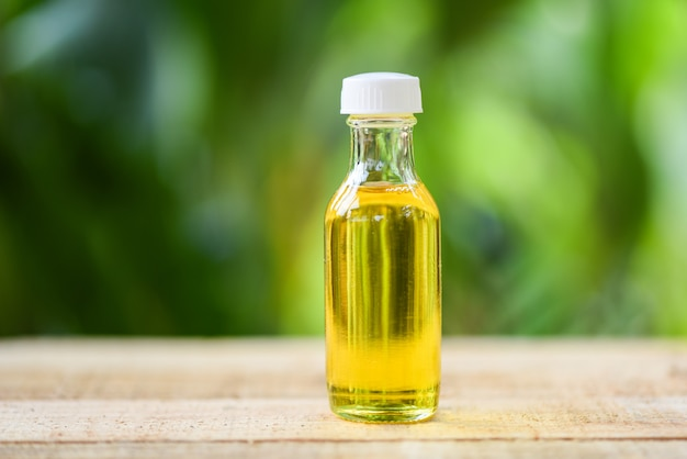 Óleo de gergelim em garrafas de vidro na madeira e natureza verde