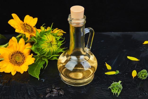Óleo de girassol em frasco de vidro, sementes e flores