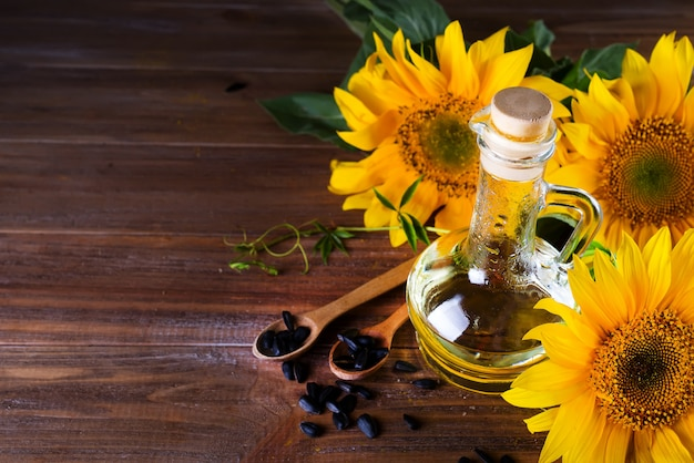 Óleo de girassol orgânico em um frasco de vidro pequeno com sementes de girassol e as flores frescas.