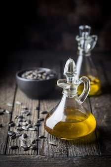 Óleo de girassol orgânico em uma pequena jarra de vidro com sementes de girassol em fundo escuro de madeira