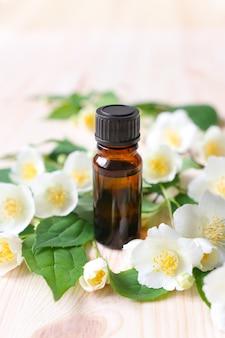 Óleo de jasmim em uma garrafa de vidro marrom e flores brancas em uma mesa de madeira