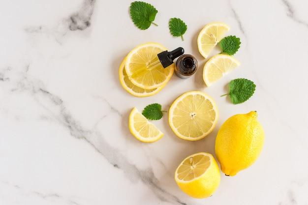 Óleo de limão em uma garrafa com um ppetka com folhas verdes de melisa e rodelas de limão sobre um fundo de mármore branco. vista do topo. efeito hidratante e anti-estrias.