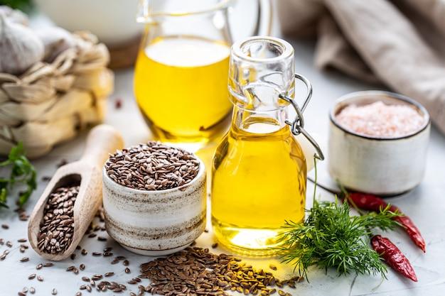 Óleo de linhaça em uma garrafa e tigela de cerâmica com sementes de linhaça marrons e colher de pau em um branco