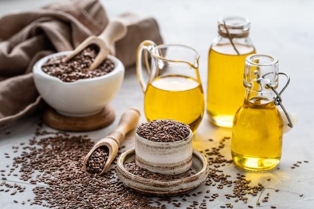 Óleo de linhaça em uma garrafa e tigela de cerâmica com sementes de linhaça marrons e colher de pau
