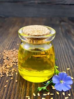 Óleo de linho em uma jarra de vidro com sementes em uma mesa e flor de linho azul em um fundo de prancha de madeira