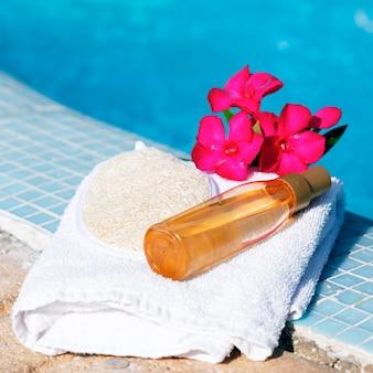 Óleo de massagem em toalha branca ao lado de uma piscina