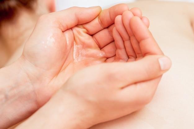 Óleo de massagem nas palmas das mãos do massageador