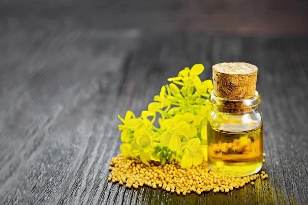Óleo de mostarda em uma garrafa de vidro, grãos e flores amarelas em uma placa de madeira