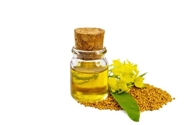 Óleo de mostarda em uma garrafa de vidro, sementes de mostarda e flores amarelas isoladas no fundo branco
