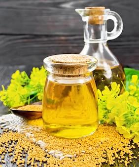 Óleo de mostarda em uma jarra de vidro e decantador, sementes de mostarda na serapilheira, flores e folhas no fundo da placa de madeira