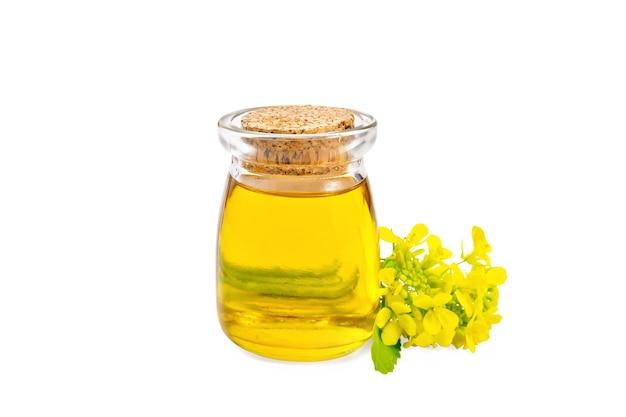 Óleo de mostarda em uma jarra de vidro, flores de mostarda amarelas isoladas no fundo branco