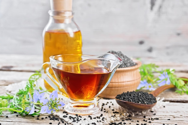 Óleo de nigella sativa em molheira e garrafa, sementes em uma colher e farinha de cominho preto em uma tigela sobre serapilheira, galhos de kalingi com flores azuis e folhas verdes no fundo de uma velha placa de madeira