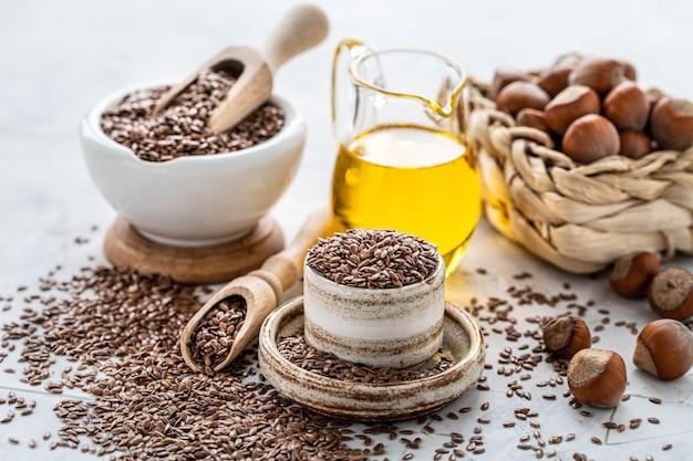 Óleo de noz e linhaça em uma garrafa e uma tigela de cerâmica com sementes de linho marrom e uma colher de pau