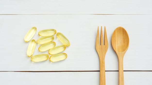 Óleo de peixe, colher e garfo em uma mesa de madeira branca.