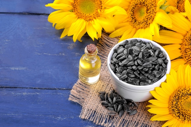 Óleo de semente de girassol e sementes de girassol com lindos girassóis amarelos no fundo em um fundo azul de madeira