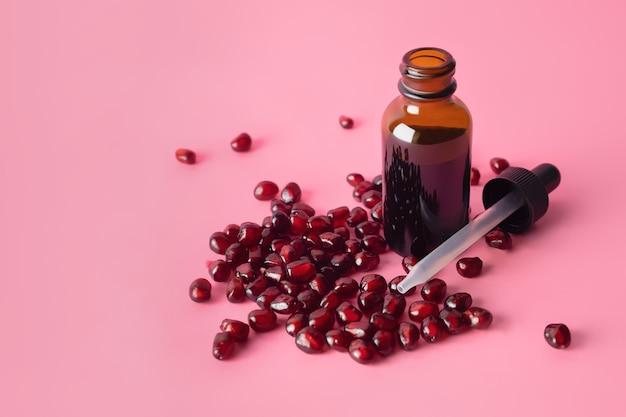 Óleo de semente de romã cosmético orgânico em frasco conta-gotas marrom na superfície rosa.