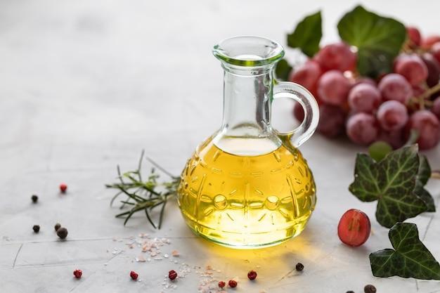 Óleo de semente de uva em uma garrafa de vidro com um cacho de uvas