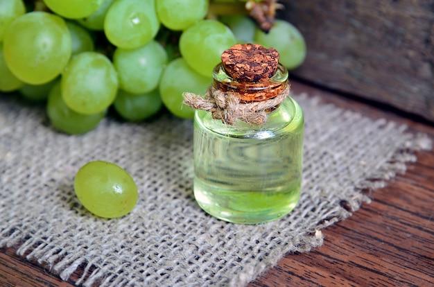 Óleo de sementes de uva em uma jarra de vidro e uvas frescas
