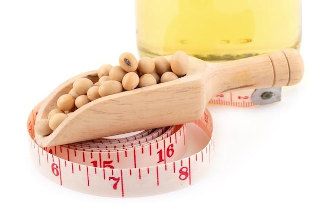 Óleo de soja, feijão de soja e medição branca da fita isolada no fundo branco. fruta saudável