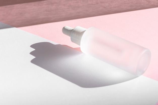 Óleo de soro com colágeno e peptídeo em frasco transparente branco com conta-gotas em fundo rosa com