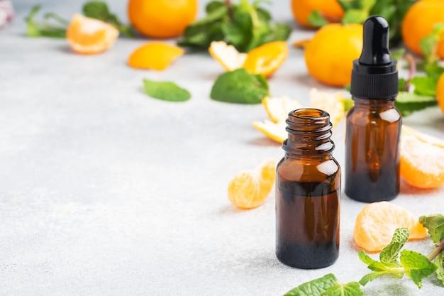 Óleo de tangerina aromática em uma bolha escura, óleo cosmético de mandarim em um fundo cinza claro, copie o espaço.