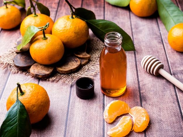Óleo de tangerina aromático, com tangerinas numa superfície de madeira