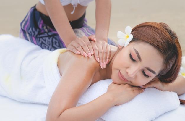 Óleo de tratamento de massagem de spa de mulher asiática bonita na praia