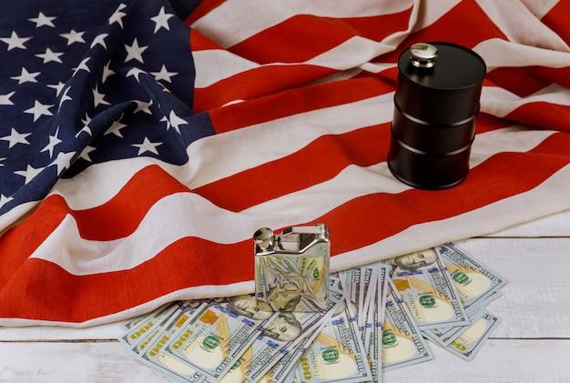 Óleo do barril de petróleo preto de cem notas de dólar dos eua em uma bandeira dos eua