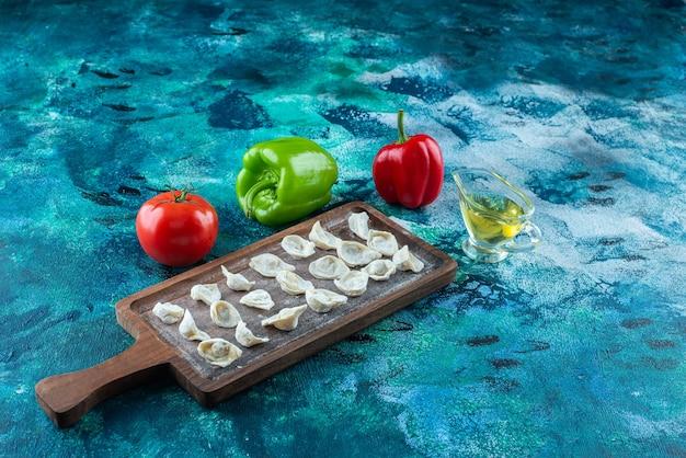 Óleo e vegetais ao lado de ravióli turco em uma placa, na mesa azul.
