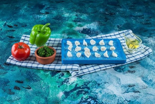 Óleo e vegetais ao lado de ravióli turco em uma placa sobre o pano de prato, na mesa azul.