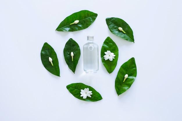 Óleo essencial com flor de jasmim em fundo branco.