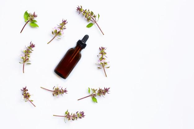 Óleo essencial com flor de manjericão doce em branco