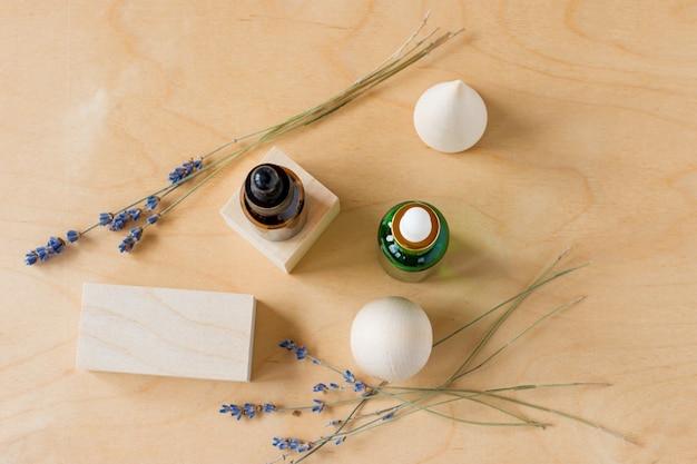 Óleo essencial com um conta-gotas e ramos de lavanda em um fundo de madeira com cubos de madeira. frasco cosmético de vidro marrom e verde, soro. vista do topo.