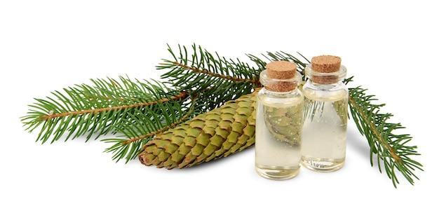Óleo essencial de abeto em garrafa e ramos de abeto isolados no fundo branco
