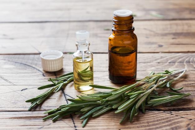 Óleo essencial de alecrim em uma garrafa de vidro com erva de alecrim fresco ramo