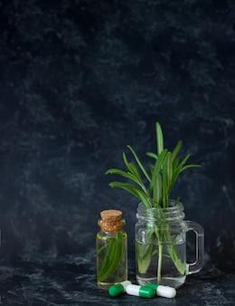 Óleo essencial de alecrim natural, folhas frescas e cápsulas de ervas para beleza e spa em fundo escuro com espaço de cópia