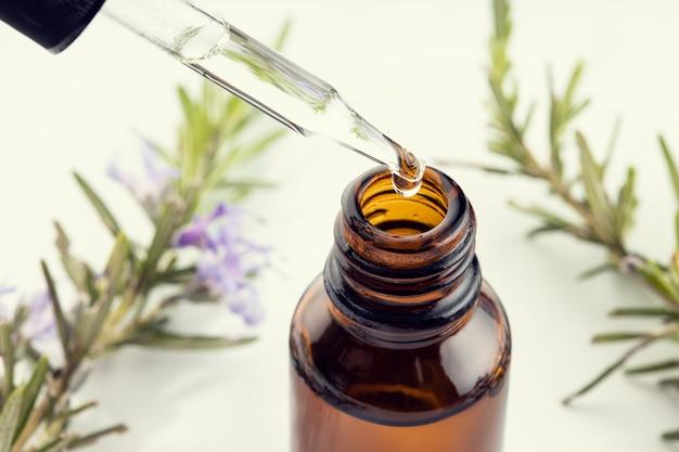 Óleo essencial de alecrim. perto de uma pipeta, garrafa âmbar e ramo de alecrim na superfície branca. remédios herbais