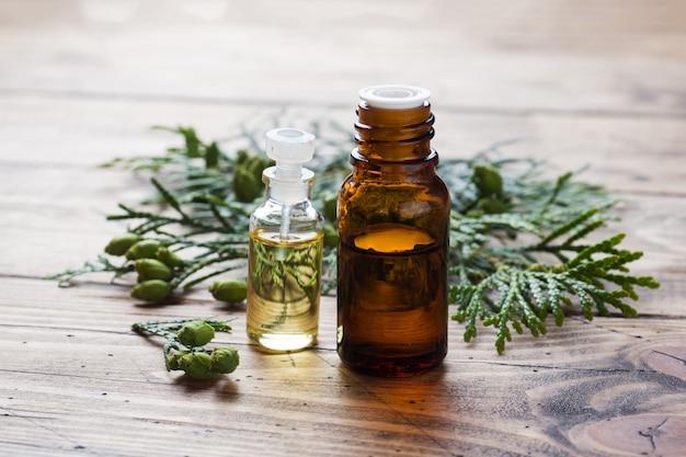 Óleo essencial de aroma de thuja em uma jarra de vidro na superfície de madeira