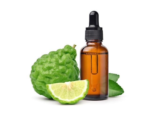 Óleo essencial de bergamota com fruta bergamota isolada no fundo branco.