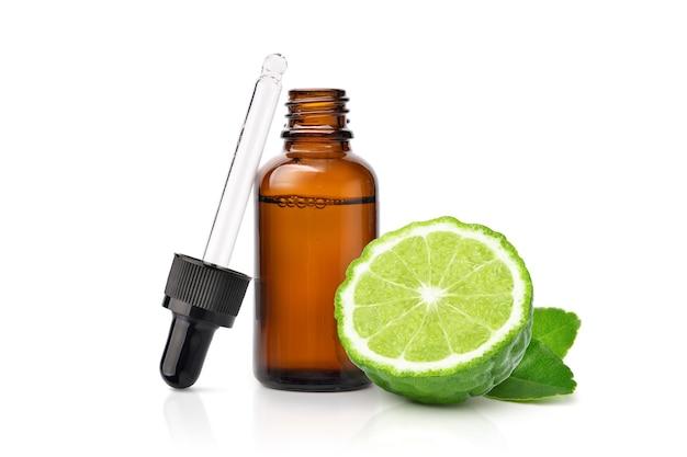 Óleo essencial de bergamota com frutas de bergamota cortadas ao meio em branco.