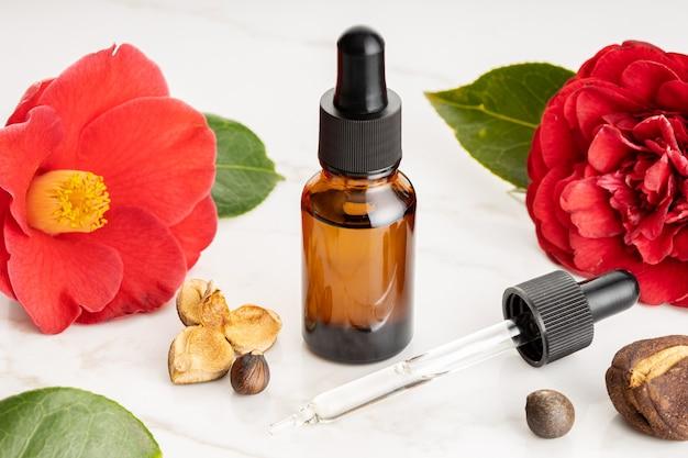 Óleo essencial de camélia. flor de camélia, sementes e frasco de vidro de óleo para beleza, cuidados com a pele, bem-estar. remédios herbais