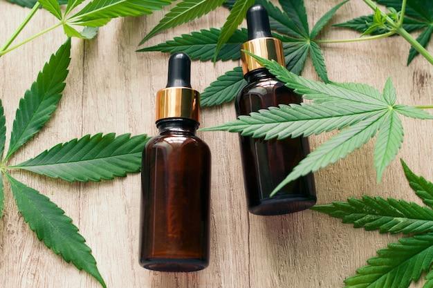 Óleo essencial de cânhamo herbal natural em uma garrafa de vidro e folhas verdes de maconha