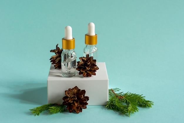 Óleo essencial de cedro e abeto em pequenas garrafas de vidro no pódio da moda sobre fundo azul.