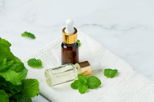 Óleo essencial de hortelã-pimenta em garrafa com hortelã-pimenta verde fresca