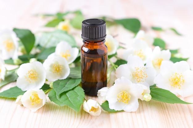Óleo essencial de jasmim em um frasco de vidro marrom em um fundo de madeira com flores