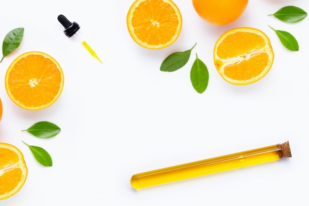 Óleo essencial de laranja cítrica e folhas isoladas no branco