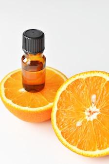 Óleo essencial de laranja cítrica em frasco de vidro escuro com frutas frescas de laranja