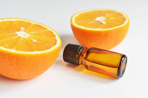 Óleo essencial de laranja cítrico em frasco de vidro escuro com frutas frescas de laranja
