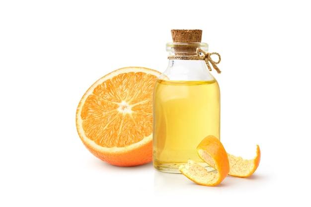 Óleo essencial de laranja com fruta laranja e casca isolada no fundo branco.